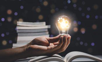 Hand,Held,Light,Bulb,On,The,Book,And,Light,Bulb