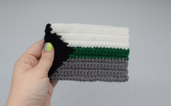 Hand holding a crochet demiromantic pride flag on a white background