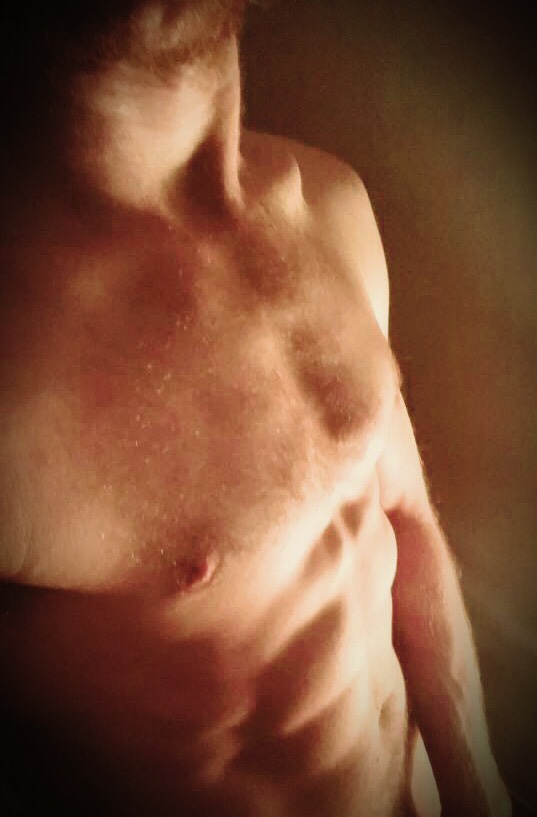 A young man's torso shines naked in the light