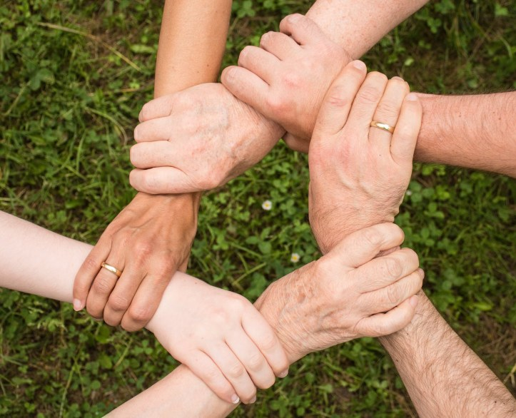Hands clasped in a circle of friendship