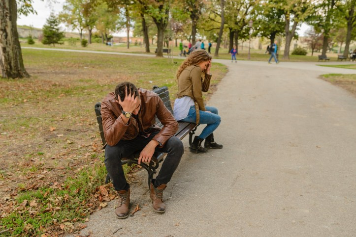 Man and woman sit with head in hand on a bench