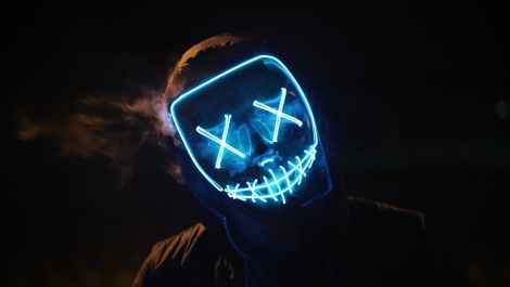 Neon faced man in hoodie with X eyes and stitch mouth, representing an internet troll