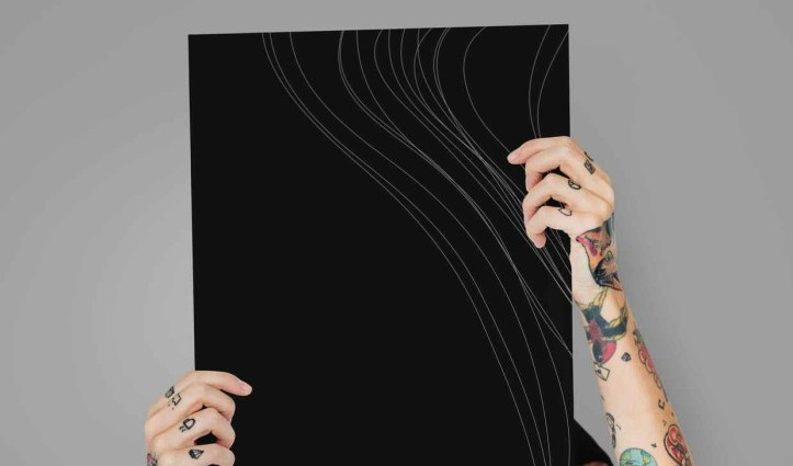 tattooed arms hide behind a black board