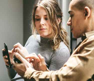 Man and woman using mobile phones to text