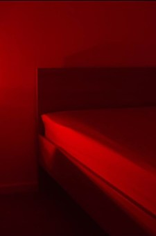 The corner of an empty bed in red light at little black book parties