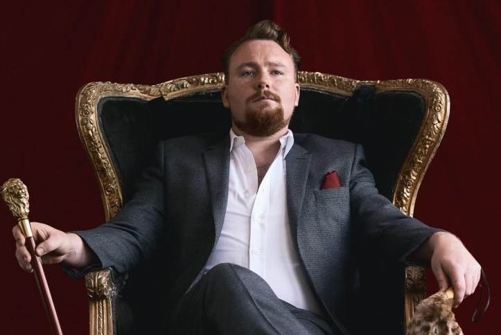 Lion Rouge, king of Roar Parties, sits on a throne in front of a red velvet curtain, holding a gold and wood cane and wearing a grey suit