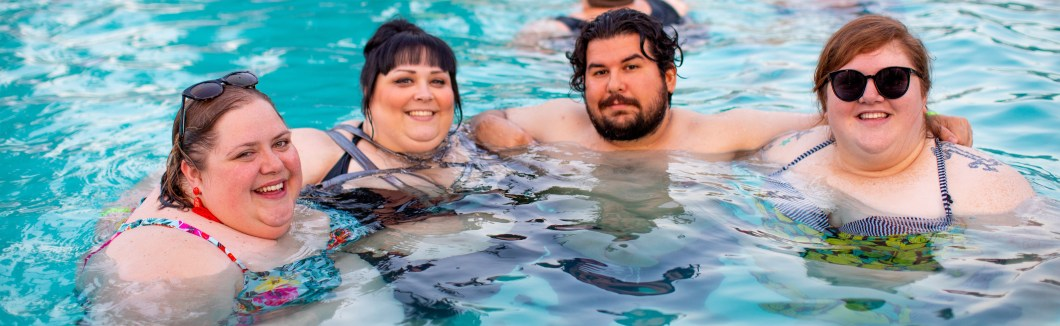 Three plus size women and one plus size man enjoying a swimming pool together