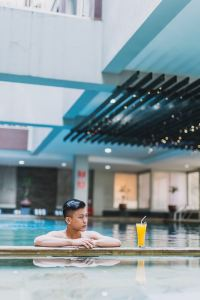 A young asian man in a swimming pool that is not Rios naturist spa in London UK.  He has a yellow drink beside him