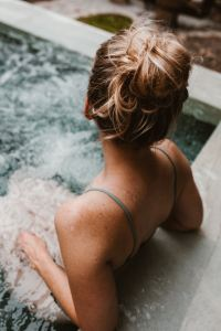 A dark blonde woman with tanned skin and freckled shoulders reclining in a Jacuzzi that is not located at Rios Spa in London UK