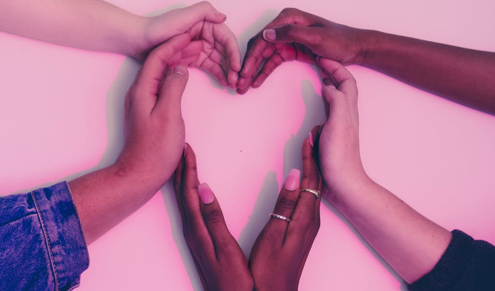 six hands of different ethnicity making a heart