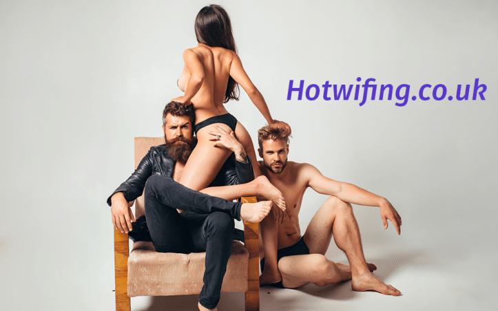 A topless woman sits with two bearded men, one in a leather jacket and one with a bare torso, in an image that suggests hotwifing