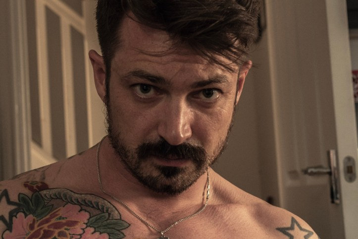 Face of online male sexworker brunette with beard and tattoos wearing necklace, facial shot