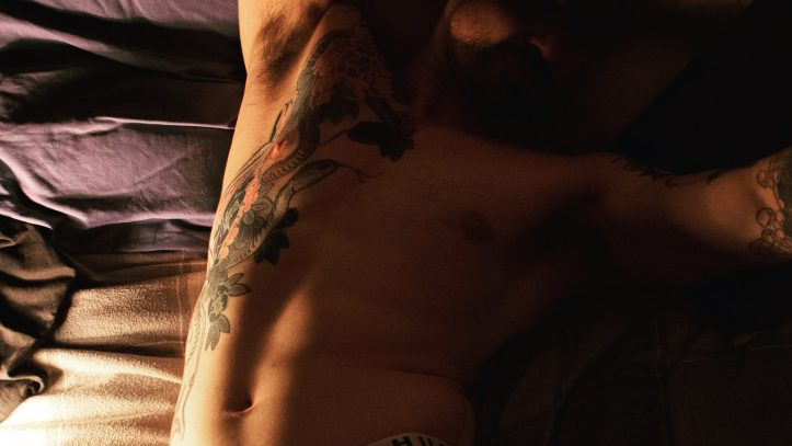 male online sexworker with tattoos poses for a shot lying on the bed with torso exposed