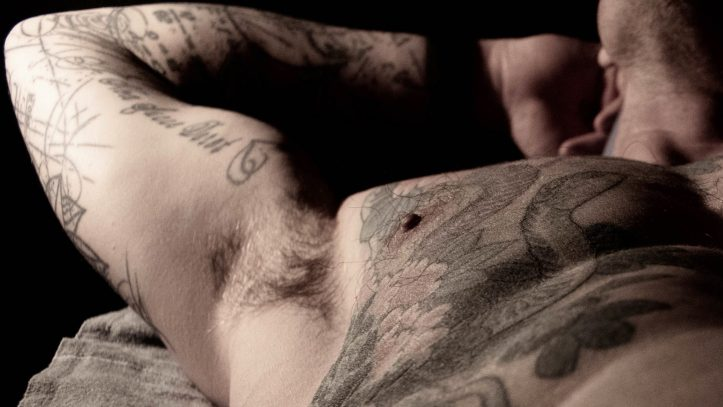 male online sexworker poses for a photo with tattooed torso and neck showing, arms behind head