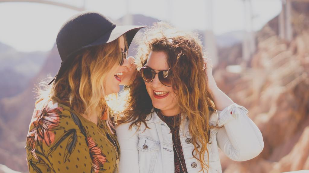 Two women with long hair laughing outside.
