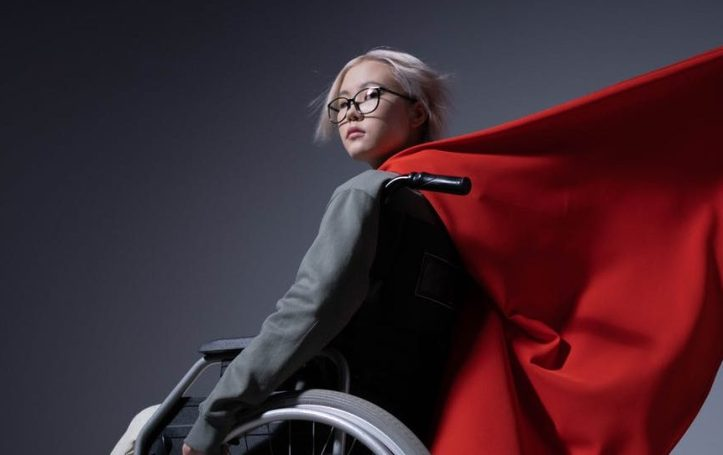 girl in wheelchair with red cape.  Is she a hero?