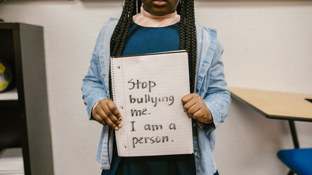 child showing message written in a notebook.  Online bullies are real too, and often adults