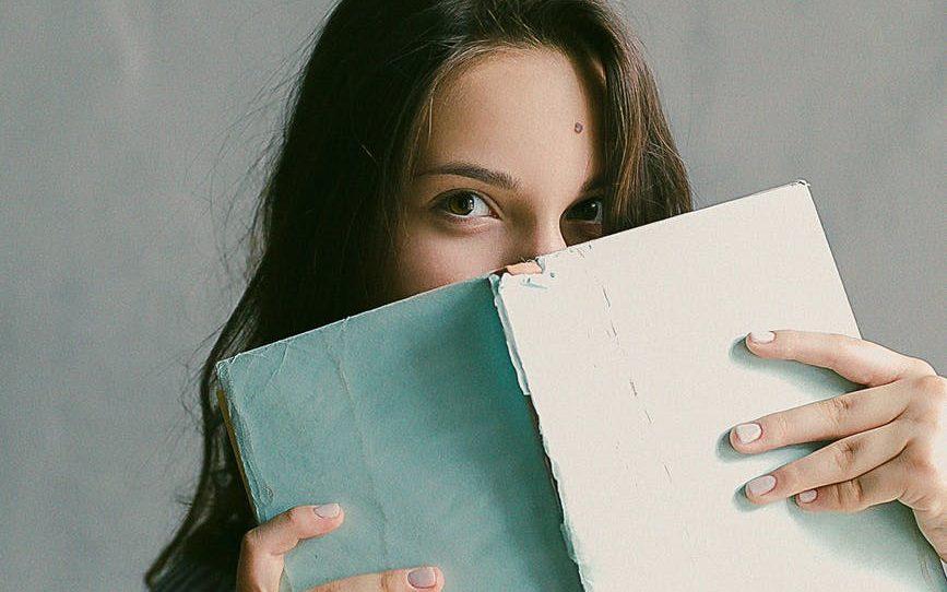 woman holding a book.  Hiding.  Is it a secret?