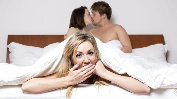 woman covers her mouth in bed while man and woman kiss behind her.  Image from 3 fun app