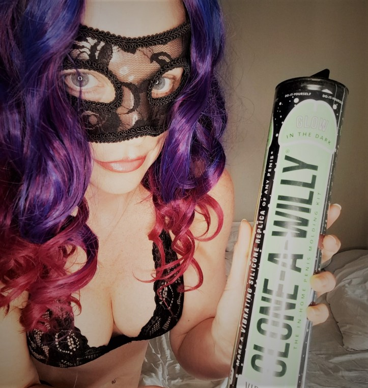 Alice Hunter smiling holding a clone-a-willy kit in black lingerie and party mask