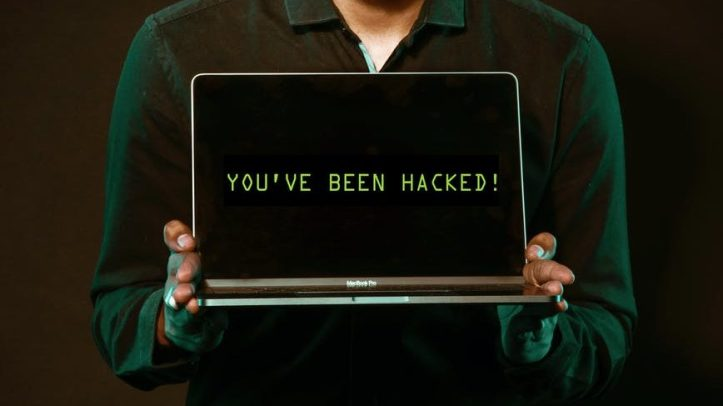 man holding laptop computer with both hands.  The internet has hacked your brain.  You are now told what to think, and people can purchase space to convince you.  We also apply this to others.  How does vaccine status affect how we view potential dates?