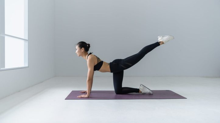 photo of asian woman doing yoga on a mat