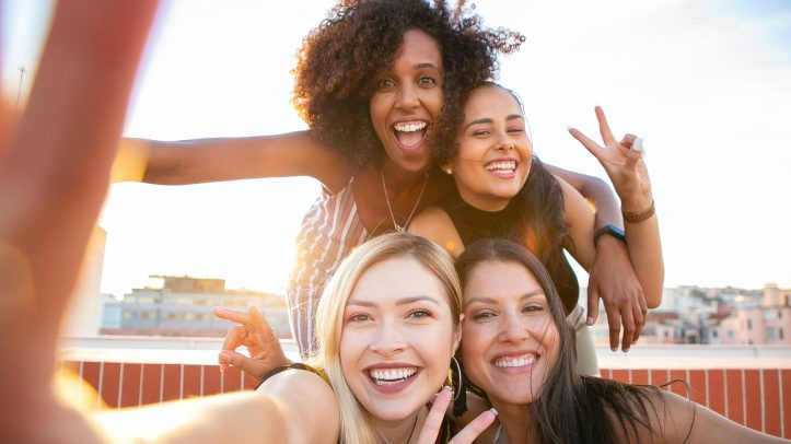 cheerful young diverse women showing v sign while taking selfie on rooftop.  People listen to their friends and family about politics and vaccinations more than anyone else