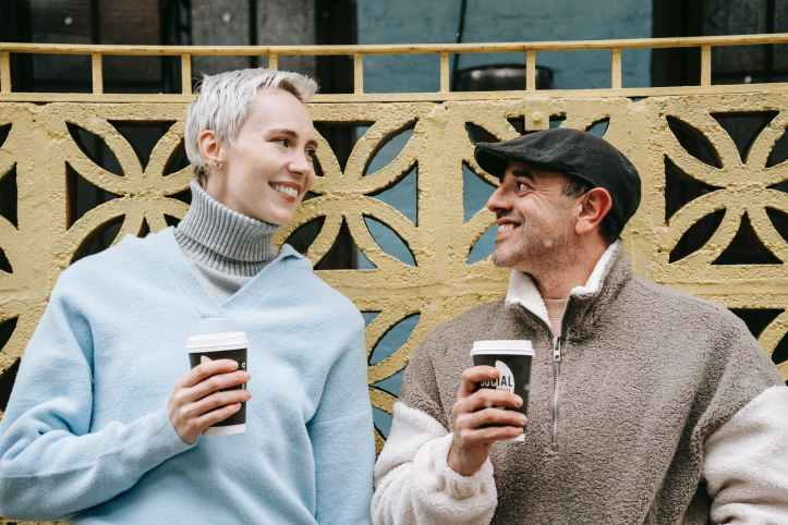 smiling couple with coffee to go on urban street