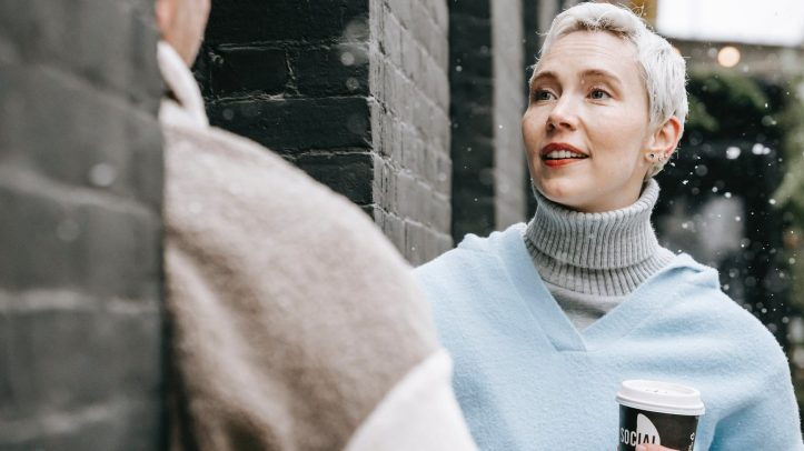 woman with takeaway coffee talking to crop boyfriend in town.  Talking to people who dont hold our opinions is a great way to learn new perspectives
