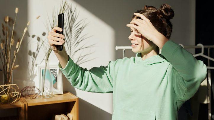 photo of girl smiling while holding black smartphone. allthingsworn.com verifies sellers