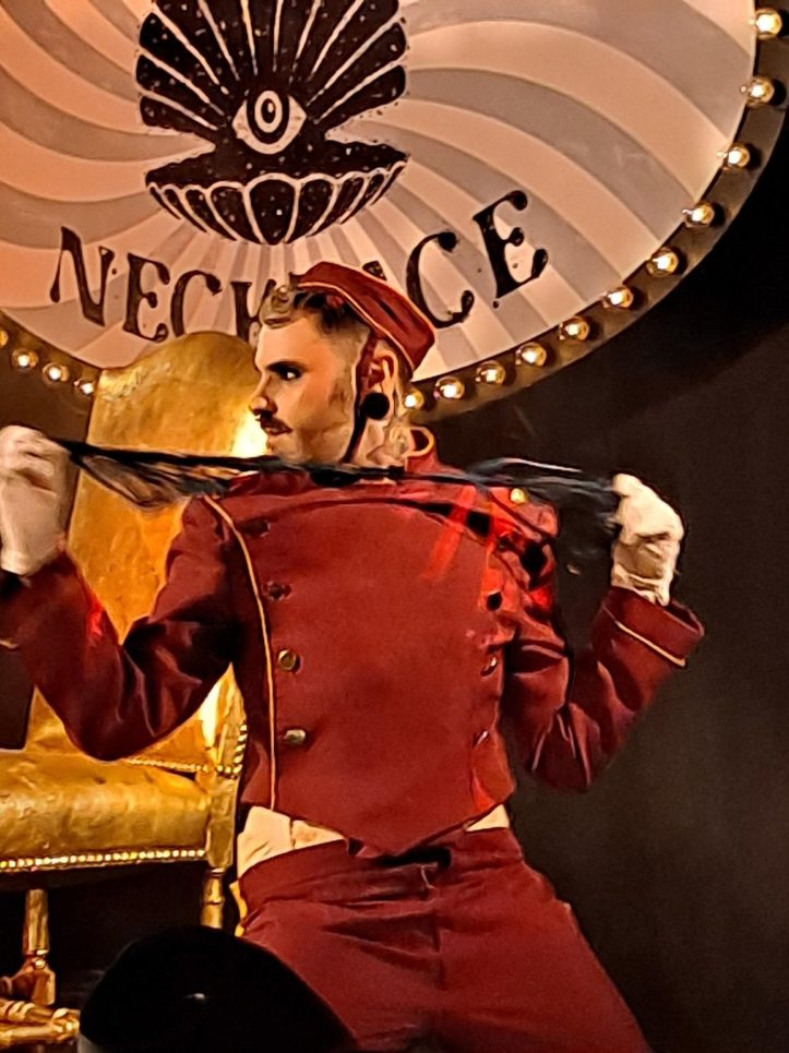 Bellhop performer with riding crop at Pearl Necklace by Torture Garden performing
