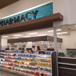 Universal Custom Display UCD Grocery Displaying Pharmacy In Supermarket Showcasing Pharmaceutical Products On Shelves With Blue Pharmacy Sign At Top