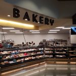 Universal Custom Display UCD Grocery Displayed In Supermarket Showcasing Different Cakes With Bakery Sign At The Top With Bakers Working In The Background