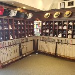 Universal Custom Display UCD Retail Golf Showcasing Golf Hats On The Wall At The Top With Golf Clubs Standing On The Ground