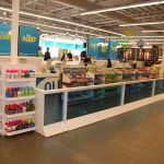 Universal Custom Display UCD Retail Cashier Entrance Line With Retail Displays Lined Up For Customers To Look At Before Buying Their Item Including Water Bottles And Candy Bars