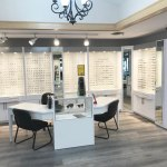 Universal Custom Display UCD Commercial Eye Glasses Wall Display With Light Backlights Showcasing Eye Glasses With Desk And Sunglass Display Case In Foreground