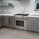 Universal Custom Display UCD Residential Custom Kitchen With Stainless Steel Ovens And Table Top Gas Burners And Large Wooden Drawers With White Wallpaper Background
