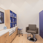 Universal Custom Display UCD Commercial Health Professional Office With Wooden And Blue Shelving Sitting On Top Of Wooden Drawers With White Counter Space
