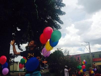 Menino soltando balão na revoada