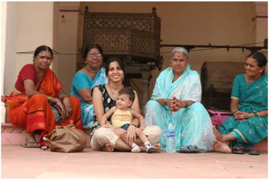 Modern-Indian-Women-Sitting-Surrounded-By-Traditional-Indian-Women-Wearing-Saree