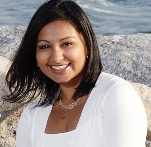 Dr. Rashmi Mullur sits on the beach, smiling. She is wearing a white top, diamond necklace, and her shoulder-length black hair is down.
