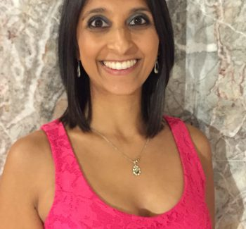 Anisha Gangotra wears a bright pink tank top and stands against a granite wall, smiling happily.