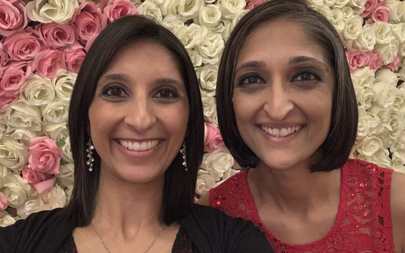 Anisha Gangotra and Trishna Bharadia stand side-by-side against a wall of pink-and-white roses. Both are smiling. Anisha, on the left, has shoulder-length straight black hair and wears a black top, dangling earrings and a delicate necklace. Trishna, on her right, has chin-length straight black hair with some grey streaked through it. She wears a textured red top. Both have medium brown skin.