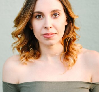 Lara Parker has shoulder-length curled brunette hair, parted in the middle and worn down. Her white skin is illuminated in the sunlight. She is wearing an off-the-shoulder khaki green top. She looks directly into the camera.