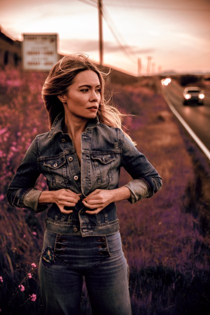 Brooke Geahan stands among the wildflowers by the side of a road. She looks into the distance as the wind blows through her long blonde hair. She is buttoning her denim jacket. The color palette is muted and dramatic.