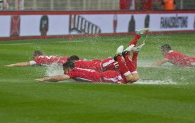 Players sliding on the waterlogged pitch
