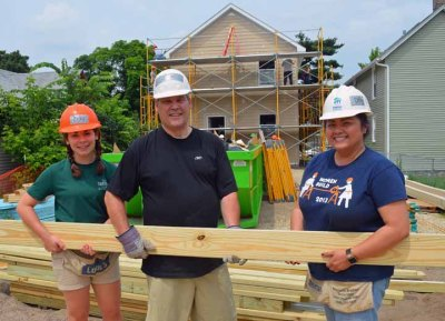 Erica Brown (L), Jim Giebel and Dolly Lee haul lumber on the site.