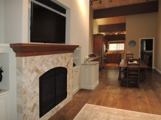 Cherry mantel with stone face, inset TV above.