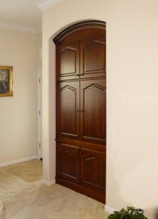 Alder wood inset TV cabinet with pocket doors and arched crown molding.