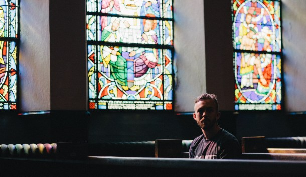 White male with beard, sitting in church pew alone, surrounded by stained glass windows